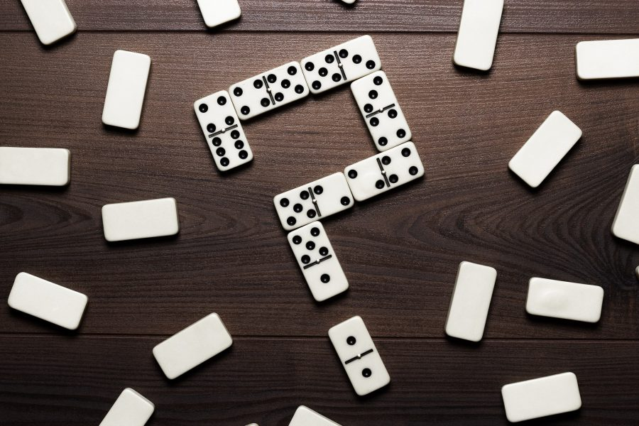 Domino Pieces Forming Question Mark On Wooden Table