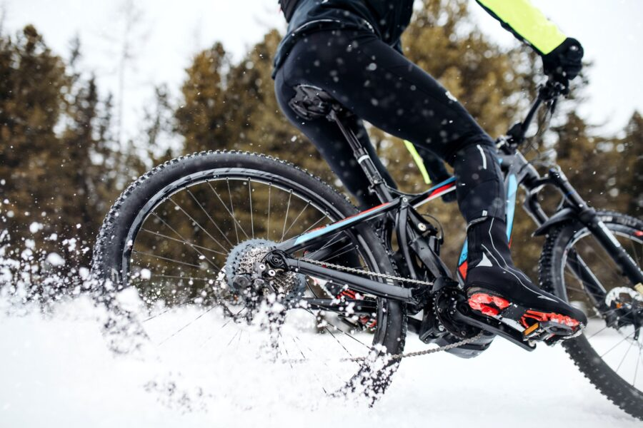 Midsection of mountain biker riding in snow outdoors in winter